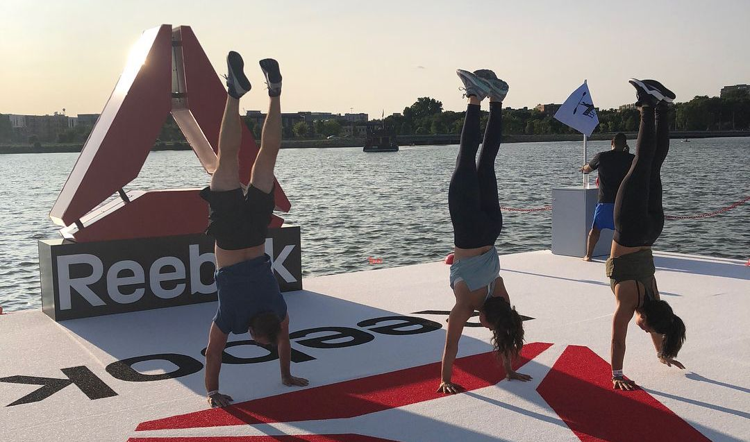 3 people doing a handstand by a pier at a Reebok event