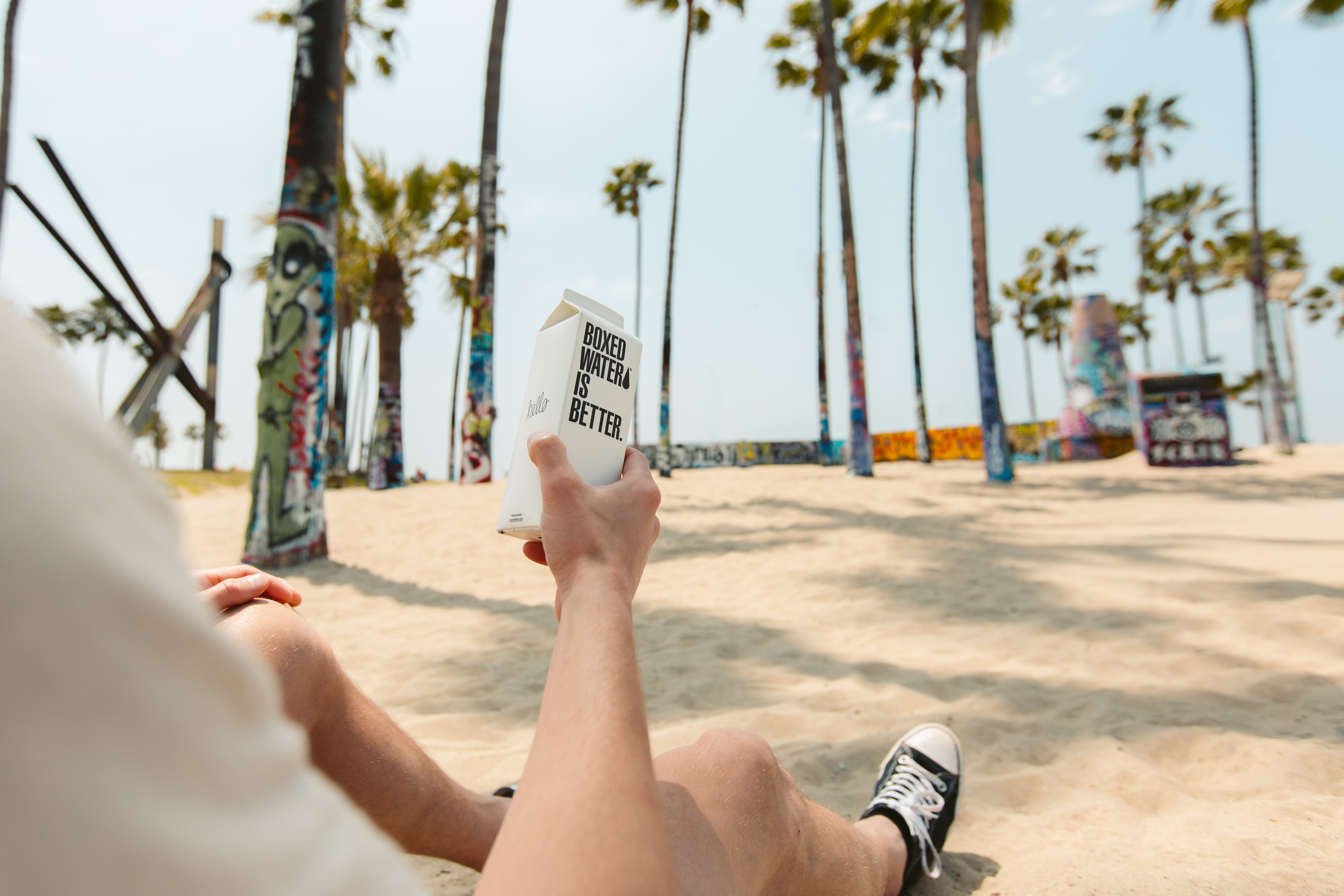 Person sitting on a beach with a box of Boxed Water Is Better